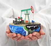 Eco-concept. A cut planet with oil pumpjack in woman's hands iso. Eco-concept. A cut planet with oil pumpjack in woman's hands  on a white background. The Stock Images