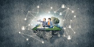 Two kids of school age with book exploring this great world Stock Photos