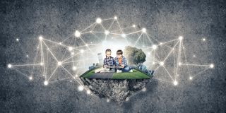Two kids of school age with book exploring this great world Royalty Free Stock Images