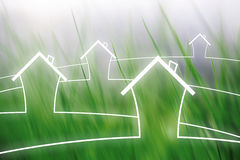 Eco concept houses on blurred grass background Stock Image