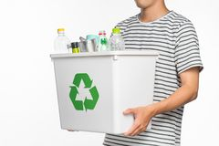 Eco concept. Male hands holding recycling bin full of recyclable. Items isolated on a white background Royalty Free Stock Image