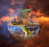 Eco-concept. Oil pump on a cut planet on moody background. The c. Oncept of natural resource extraction. Save the planet Royalty Free Stock Images