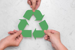Eco concept. Paper recycle sign in hands royalty free stock photography