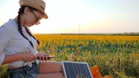 Eco, donna felice in lampadina con il telefono e pannello in mani, ragazza che per mezzo del cellulare e della batteria video d archivio