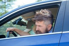 Eco driving is an ecologic driving style. Bearded man travel by automobile transport. Hipster enjoying road trip. Eco. Friendly and sustainable travel stock photo