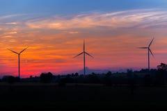 Eco-Energie im Windkraftanlagebauernhof mit Sonnenuntergang Stockfoto
