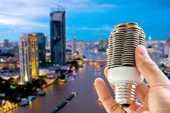 Eco energy concept. Hand holding light bulb and cityscape background, eco energy concept Royalty Free Stock Image