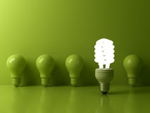 Eco energy saving light bulb , one glowing compact fluorescent lightbulb standing out from unlit incandescent bulbs. Reflection on green background Stock Photography
