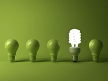 Eco energy saving light bulb , one glowing compact fluorescent lightbulb standing out from unlit incandescent bulbs. Reflection on green background Stock Photo
