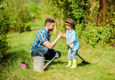 Eco farm. watering can, pot and shovel. Garden equipment. small boy child help father in farming. father and son in. Cowboy hat on ranch. happy earth day royalty free stock photo