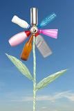 Eco flower. Recycle flower created from beer can, plastic and glass bottles and waste paper stem spelling reduce-reuse-recycle over blue sky Stock Photo