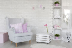 Eco-friendly baby room decor in white. Fragment of a baby room with a white brick wall and DIY furniture made of wooden boxes Stock Photo