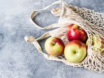 Eco-friendly beige shopping bag with red apples on a gray background. String bag with fruits. Zero waste, no plastic concept. Copy royalty free stock photography