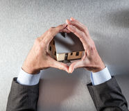 Eco-friendly building protection with businessman hands embracing a house. Concept of home security or eco-friendly building protection with businessman or real Royalty Free Stock Photography