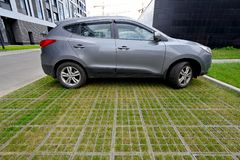 Eco-friendly car parking of concrete cells and turf grass. Car on a modern outdoor parking made from concrete cells and turf grass stock photos