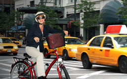 Eco-friendly commuter. Business woman taking the  bicycle to work through the busy city streets Stock Images