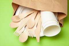 Eco-friendly disposable utensils made of bamboo wood and paper on a green background. Draped spoons, fork, knives. Bamboo bowls with paper cups and packet stock photo