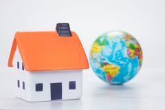 Eco-friendly efficient house concept with globe. Eco-friendly efficient household energy and fuel concept with a world globe alongside a toy model over a white Royalty Free Stock Photos