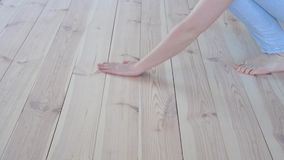 Eco-friendly flooring - woman with bare feet strokes the warm wooden floor closeup.