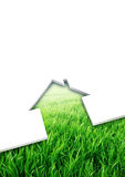 Eco friendly house concept. Cutting of a blank sheet, house shaped above a green field background Stock Images