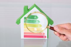 Eco friendly house concept. Inspecting new eco friendly house using magnifying glass Stock Images
