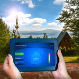 The eco-friendly house in the mountains. Tablet controled temperature in house Royalty Free Stock Photography
