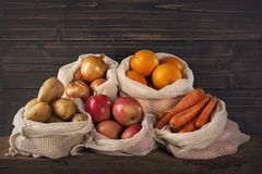 Eco friendly reusable net bags. With fruits and vegetables stock photos