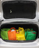Eco-Friendly Trunk. Four colorful eco-friendly shopping bags filled mostly with groceries.  Copy space on black underside of opened trunk lid Stock Image