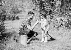 Eco gospodarstwo rolne podlewania puszka, garnek i ?opata, Ogrodowy wyposa?enie ma?y ch?opiec dziecka pomocy ojciec w uprawia? zi zdjęcia royalty free