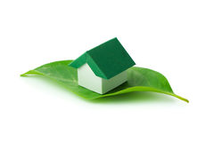 Eco green house. Miniature green house on leaf over white background Royalty Free Stock Image