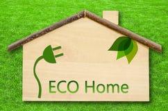 Eco hem på liten hem- trämodell på bakgrund för grönt gräs Royaltyfria Bilder