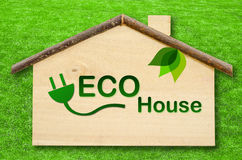 Eco home. Eco home on Little home wooden model on green grass background. Save clipping path Royalty Free Stock Image