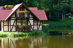 Eco house. Concept - timber building standing on lake Royalty Free Stock Images