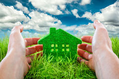Eco House. In green grass protected by the human hands on blue sky background Stock Photos