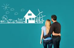 Eco house concept. Happy embracing couple looking at eco friendl stock photos