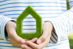 Eco house icon. Hand holding eco house icon Stock Images