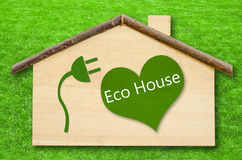 Eco house on Little home wooden model. On green grass background. Save clipping path Stock Image