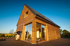 Eco house. Man standing outside modern new eco house Stock Images