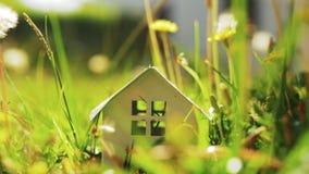 Eco-huis metafoor met huismodel in groen gras stock footage