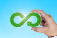 eco K??kowa gospodarka Ręka trzyma zielonej trawy nieskończoności strzały symbol obraz stock