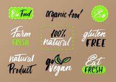 Eco labels set on craft background. Modern brush lettering eco f. Ood tags. Vegan, farm fresh, organic food, bio food,eat fresh, go vegan, natural product Royalty Free Stock Photography