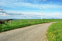 Eco landscape with country road and wind turbine Royalty Free Stock Photo