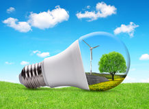 Eco LED bulb with solar panel and wind turbine. Royalty Free Stock Image