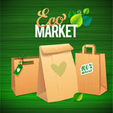 Eco Market Promo.  Paper bags and leaves on green Stock Photography