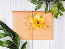 Eco paper envelope with yellow orchid flowers and green leaves stock photo