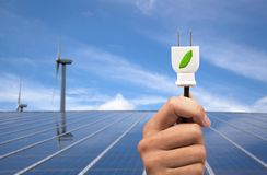 Eco power concept. Hand holding green power plug and solar panel and wind turbine background Stock Images