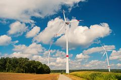 Eco power, green technology concept. Wind farm in Lower Saxony, Germany. Global warming, climate change. Alternative energy source. Turbines on field on cloudy stock photo