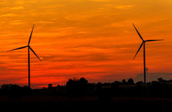 Eco power in wind turbine farm with sunset Royalty Free Stock Photography