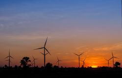 Eco power in wind turbine farm with sunset Royalty Free Stock Images