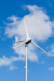 Eco power, wind turbine generating electricity. Against partly cloudy blue sky background, green earth concept royalty free stock photos